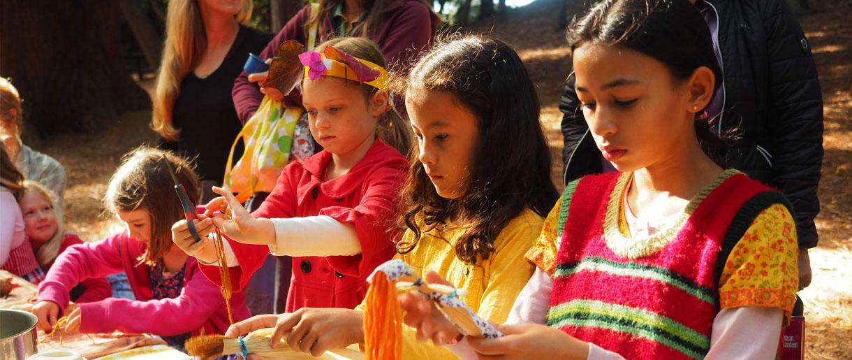 Children making husk dolls during harvest faire
